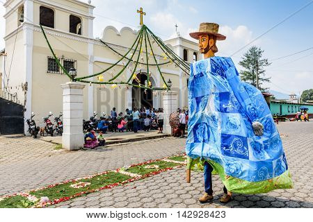 Parramos Guatemala - May 29 2016: Giant puppet folk dancer called a gigante walks past church & processional carpet during Corpus Christi mass.