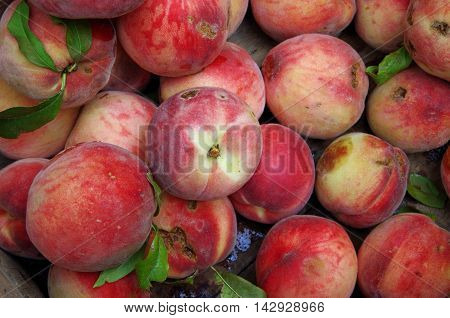 Farm fresh organic peaches with  green stems and leaves in market display
