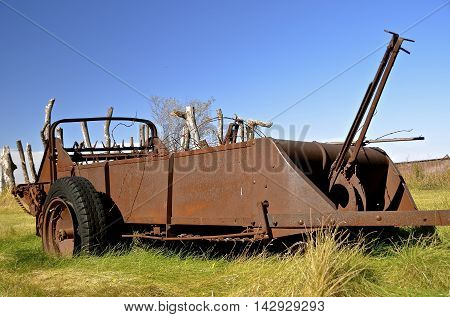 An old pull rusty manure spreader parked in a pasture of long grass