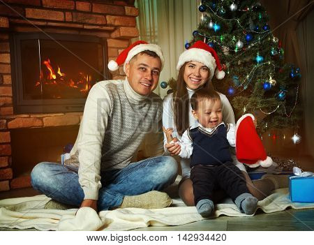 young family celebrating Christmas at home. father, mother and child in Santa hats. New Year and xmas people