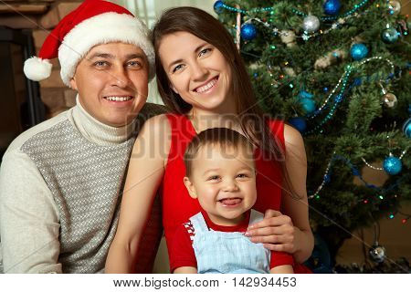 portrait of a young family celebrating Christmas at home. father, mother and child in Santa hats. New Year and xmas people