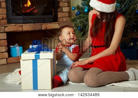 mother and child at Christmas time. Mom gives baby a gift. New Year and xmas people