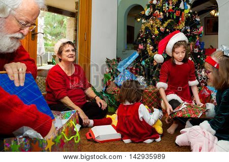 Grandparents and their grandchildren sit on a living room floor in front of a big decorated Christmas tree and unwrap Christmas presents.