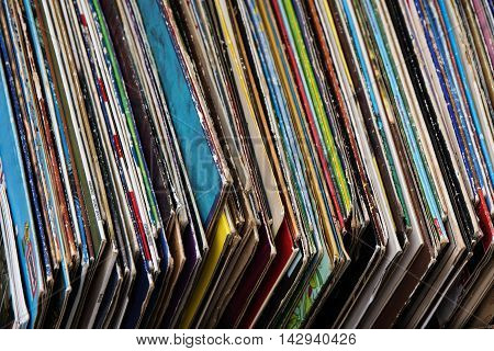 abstract background from old phonograph records in their cases placed for sale at a flea market for nostalgic collectos selected focus narrow depth of field