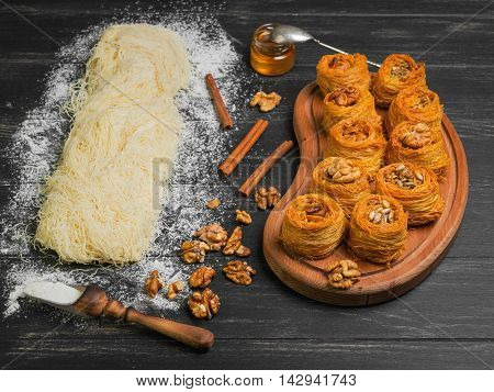Cooking sweets turkish traditional ramadan pastry dessert kunafa (kadaif baklava) ingredients dough nuts walnuts peanuts sunflower seeds honey cinnamon dark black wood background