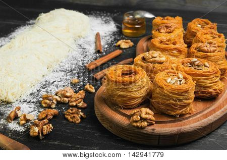 Cooking sweets turkish traditional ramadan pastry dessert kunafa (kadaif baklava) ingredients dough nuts walnuts peanuts sunflower seeds honey cinnamon dark black wood background poster