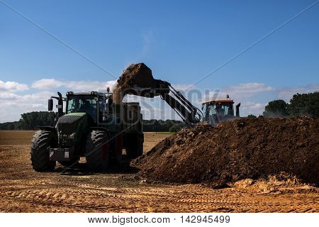 fertilize the field excavator with shovel fills organic fertilizer or manure in the trailer of a tractor blue sky copy space