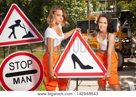 Two Women In Orange Overalls Are Mounting