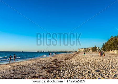 Adelaide Australia - February 11 2016: People walking along the Glenelg Beach at sunset