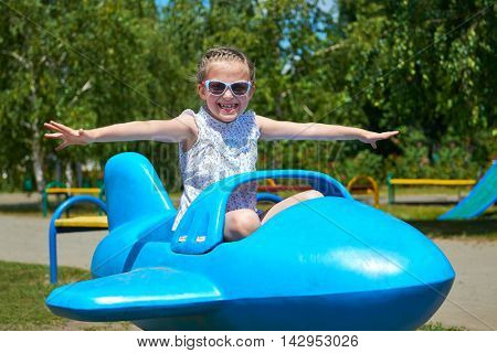 child girl fly on blue plane attraction in city park, happy childhood, summer vacation concept