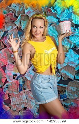 A smiling pretty girl with loose long blond hair is holding a bucket of paint  in her left hand. Her right hand is showing everithing is OK! She is standing in the unusual  colorful background of newspapers
