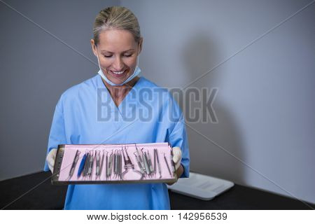 Smiling dental assistant holding tray with equipment in dental clinic