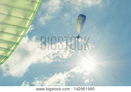 Low Angle In Sun Light Of Paragliders