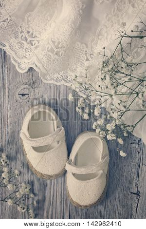 White baby girl shoes on a wooden background