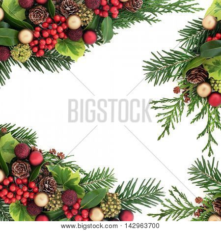 Decorative christmas border with red and gold bauble decorations, holly and berries, ivy, pine cones, cedar cypress  and fir leaf sprigs over white background with copy space.