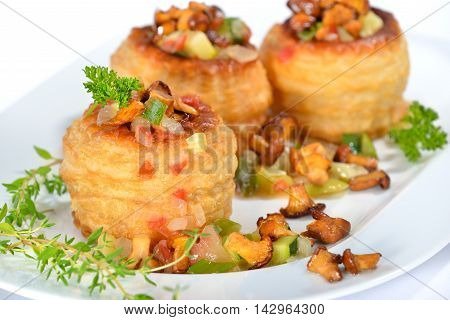 Puff pastry pie stuffed with zucchini vegetables with thickened sauce and  fresh chanterelles