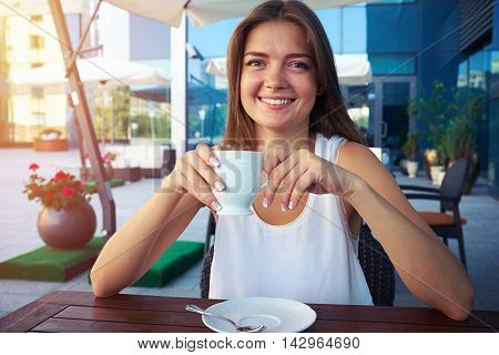 Young girl is sitting relaxed at the outdoors cafe and drinking a cup of aromatic coffee during her lunchtime