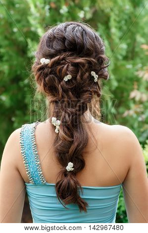 elegant hairstyle with fresh flowers in a plait . Woman with fashion festive hairstyle on nature background. Hairstyle. Wedding flower decorations in the hair of the bridesmaid