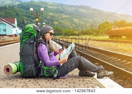 Happy girl tourist with backpack sits on a platform waiting for a train. Travel concept. Traveler holding map waiting for a train and planing for next trip. Traveler reading map