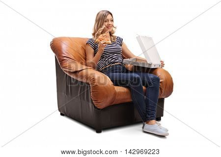 Young woman seated on an armchair having a slice of pizza and watching tv isolated on white background
