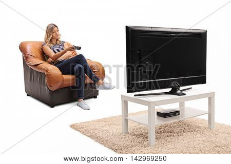 Bored woman seated on an armchair watching something dull on television isolated on white background