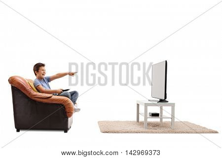 Laughing child seated on an armchair watching something hilarious on tv isolated on white background