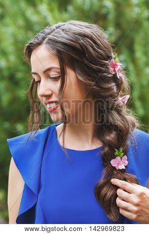 elegant hairstyle with fresh flowers in a plait. Portrait of woman with fashion hairstyle for holiday on nature background. Hairstyle. Wedding flower decorations in the hair of the bridesmaid