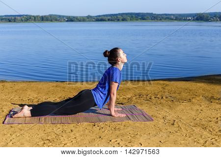 Yoga girl in cobra pose on the river bank . Woman meditating with her eyes closed while doing cobra pose. Young woman practicing yoga on mat outdoors. Healthy lifestyle. Yoga. Cobra pose bhujangasana