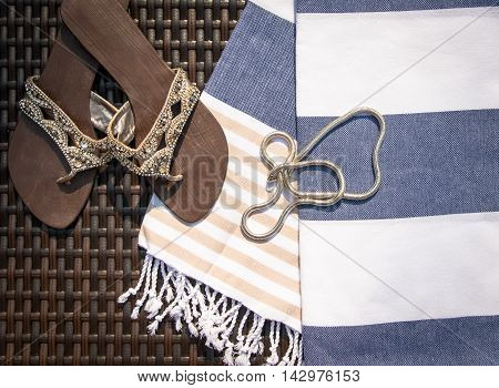 Concept of flat lay summer accessories of white, blue and beige Turkish towel, modern white gold necklace, brown leather ladies sandal with glass stone embroidery on rattan lounger.