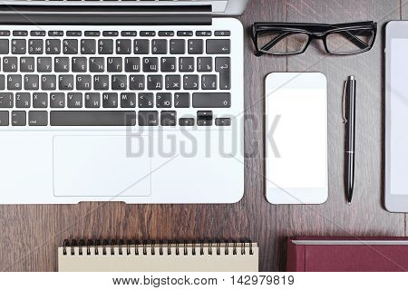 Top view and closeup of wooden office desktop with laptop keyboard blank white mobile phone screen spiral notepad book pen and glasses. Mock up