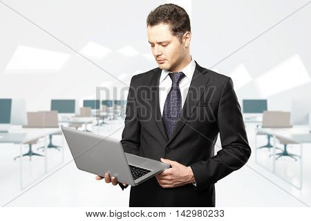 Handsome businessman looking at laptop screen in coworking office interior