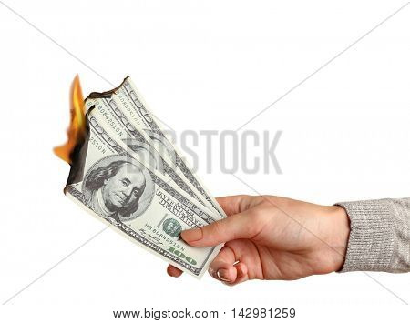 Female hand holding burning dollar banknotes on white background.