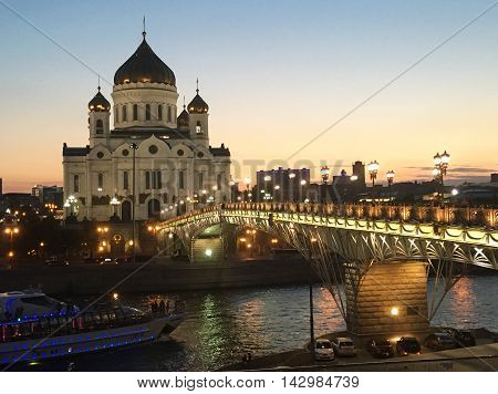 Moscow Russia- June 20 2016: Majestic orthodox Cathedral of Christ Saviour illuminated at dusk on bank of Moscow river and cruise boat. It is tallest Orthodox church in world