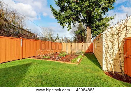 Small Vegetable Garden With Risen Beds In The Fenced Backyard Near House.