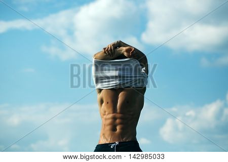 Sexy Muscular Man Undressing On Sky Background