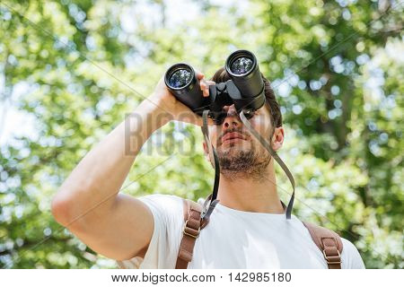 Concentrated young man with backpack looking through binoculars in forest