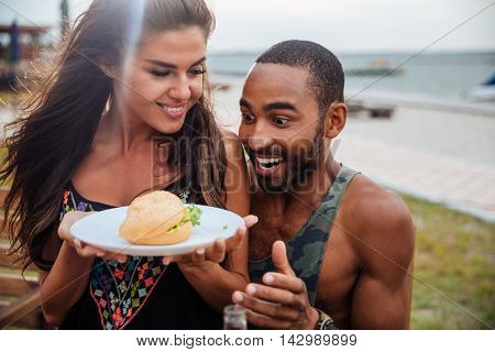 Young afro man looking hungry and looking at the burger on a plate