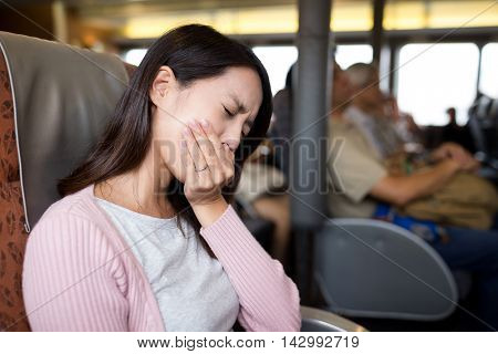 Woman feeling unwell and sitting on the ferry