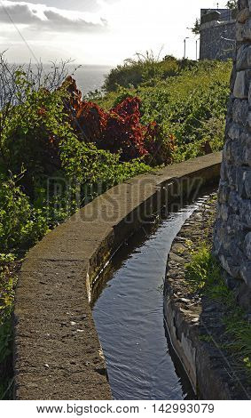 Levada irrigation channel with footpath past houses on outskirts of Funchal Madeira Portugal