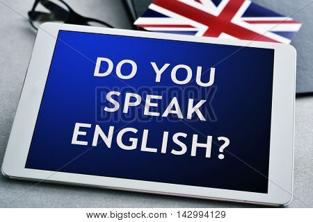 closeup of a tablet computer with the question do you speak English? in its screen, a pair of eyeglasses, a book and the flag of United Kingdom on a gray surface