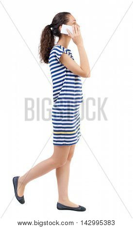 side view of a woman walking with a mobile phone. beautiful curly girl in motion.  backside view of person.  Rear view people collection. Isolated over white background. Swarthy girl in a checkered