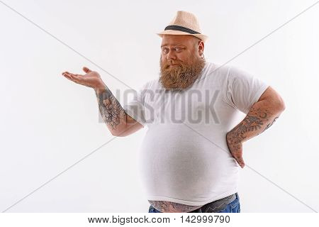 Fat man with beard is presenting something with confidence. He is standing and stretching arm sideways. Isolated on background