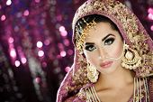 Portrait of a beautiful female model in ethnic Indian Pakistani bridal costume with heavy makeup and jewellery in landscape orientation poster
