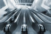 People on a moving escalators in the business center. Motion blur and blue tone image poster