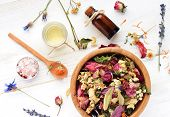 Herbal blend of various dried medicinal flowers, essential oil, bottle, sea salt. Natural skincare. Top view, focus on wooden bowl with colorful plants. poster