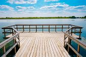 Close View Of Wooden Boardwalk Batten Viewing Platform Area Above The Water Of Lake River In Summer Spring. Panoramic Landscape And Scenic Sky With White Lush Clouds Background. poster