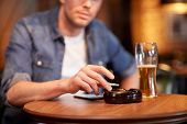people, nicotine addiction and bad habits concept - close up of man drinking beer, smoking cigarette and shaking ashes to ashtray at bar or pub poster