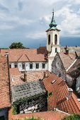 Annunciation church and red roofs of old houses Szentendre Hungary. Religious architecture. Beautiful place. Vertical composition. Place of worship. poster