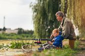 Grandfather with  grandson enjoyed on the fishing. poster