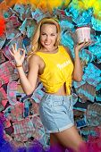 A smiling pretty girl with loose long blond hair is holding a bucket of paint  in her left hand. Her right hand is showing everithing is OK! She is standing in the unusual  colorful background of newspapers poster